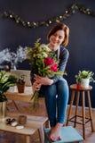 Giovane donna creativa in un negozio di fiore Una partenza dell'affare del fiorista fotografia stock