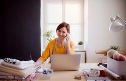 Giovane donna creativa in uno studio, facendo uso dello smartphone Una partenza di adattamento dell'affare fotografie stock libere da diritti