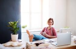 Giovane donna creativa in uno studio, riposante Una partenza di adattamento dell'affare immagine stock libera da diritti