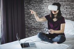 Giovane donna in cuffia avricolare di realtà virtuale o vetri 3d che gioca vid Fotografie Stock Libere da Diritti