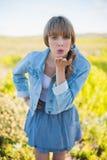Giovane donna d'avanguardia che invia bacio alla macchina fotografica Fotografia Stock