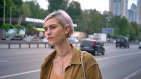 Giovane donna d'avanguardia con il taxi aspettante o il bus dei brevi capelli rosa, stante sulla via urbana vicino alla strada video d archivio