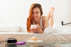 Giovane donna dai capelli lunghi che mangia prima colazione Immagini Stock Libere da Diritti