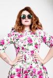 Giovane donna dai capelli rossi alla moda con capelli ricci ed il fronte grazioso che posano in occhiali da sole esprime le emozi Fotografia Stock
