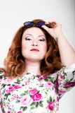 Giovane donna dai capelli rossi alla moda con capelli ricci ed il fronte grazioso che posano in occhiali da sole esprime le emozi Fotografia Stock Libera da Diritti