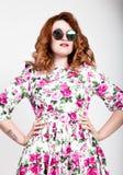 Giovane donna dai capelli rossi alla moda con capelli ricci ed il fronte grazioso che posano in occhiali da sole esprime le emozi Immagini Stock Libere da Diritti