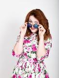 Giovane donna dai capelli rossi alla moda con capelli ricci ed il fronte grazioso che posano in occhiali da sole esprime le emozi Fotografie Stock
