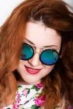 Giovane donna dai capelli rossi alla moda con capelli ricci ed il fronte grazioso che posano in occhiali da sole esprime le emozi Immagine Stock