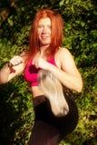 Giovane donna dai capelli rossi che combatte attacco allegro sorridente di kickboxing in natura al sole nella foresta fotografia stock
