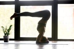 Giovane donna degli Yogi che fa esercizio del headstand di yoga fotografie stock