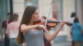 Giovane donna dei capelli neri che gioca un violino alla via pedonale stock footage