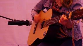 Giovane donna dei pantaloni a vita bassa che gioca una chitarra Primo piano, ragazza che gioca alla via video d archivio