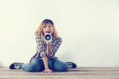 Giovane donna dei pantaloni a vita bassa che grida tramite il megafono Fotografia Stock Libera da Diritti