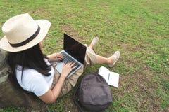 Giovane donna dei pantaloni a vita bassa che per mezzo del computer portatile mentre sedendosi sull'erba con la borsa Fotografia Stock Libera da Diritti