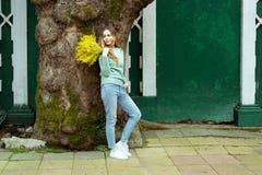 Giovane donna dei pantaloni a vita bassa che tiene un mazzo dei fiori freschi della mimosa, tempo di molla, l'8 marzo, stile di v fotografia stock libera da diritti