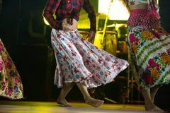 Giovane donna del ballerino a piedi nudi in vestito zingaresco che balla in scena Immagine Stock