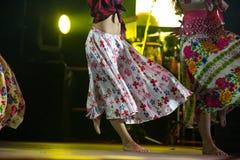Giovane donna del ballerino a piedi nudi in vestito zingaresco che balla in scena Immagini Stock