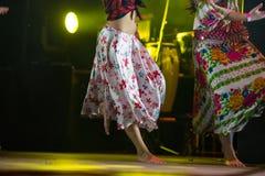 Giovane donna del ballerino a piedi nudi in vestito zingaresco che balla in scena Immagini Stock Libere da Diritti