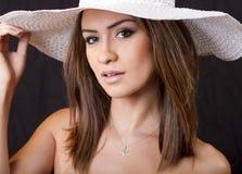 Giovane donna del brunette con il cappello di paglia bianco Fotografia Stock