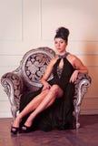 Giovane donna del brunette nella seduta nera del vestito Immagine Stock