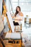 Giovane donna del pittore producendo immagine nello studio di arte Fotografia Stock
