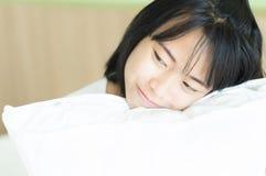Giovane donna del primo piano che abbraccia cuscino con il fronte di sorriso e la tassa felice fotografia stock