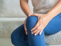 Giovane donna del primo piano che si siede sul sofà e sul ginocchio ritenente per fare soffrire e SH immagine stock libera da diritti