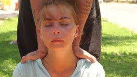 Giovane donna del ritratto che riceve massaggio del collo per dolore di trattamento nella tensione della spina dorsale e del musc archivi video