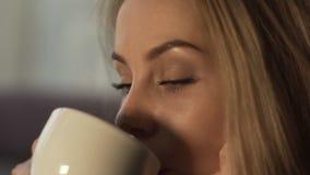 Giovane donna del ritratto con capelli biondi ed il caffè bevente o il tè di trucco perfetto video d archivio