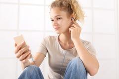 Giovane donna del ritratto con lo smartphone e le cuffie, sguardo al immagine stock libera da diritti