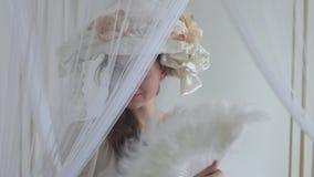 Giovane donna del ritratto in fan del cappello di seta il suo fronte con il fan della piuma bianca, nascondentesi dietro il velo  stock footage