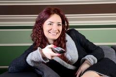 Giovane donna del sofà con la ripresa esterna della TV Immagini Stock Libere da Diritti