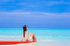 Giovane donna del surfista alla spiaggia bianca sul surf rosso fotografie stock