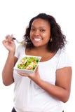 Giovane donna dell'afroamericano che mangia insalata Fotografie Stock
