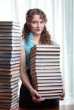 Giovane donna dell'allievo con i lotti dei libri. Immagine Stock