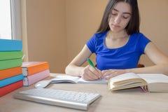 Giovane donna dell'allievo con i lotti dei libri che studia per gli esami Immagini Stock Libere da Diritti