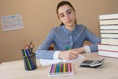 Giovane donna dell'allievo con i lotti dei libri che studia per gli esami Fotografie Stock