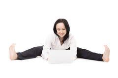 Giovane donna dell'ufficio che si siede nelle spaccature con il computer portatile sul backgr bianco Fotografia Stock