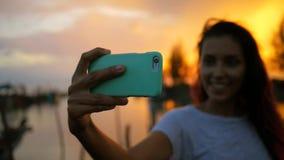 Giovane donna della corsa mista che fa Selfie al bello tramonto Ragazza Silhuette che per mezzo del telefono cellulare Rallentato stock footage