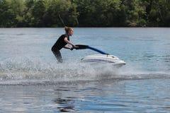 Giovane donna della foto di azione sul jet ski Immagini Stock