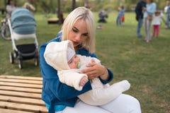 Giovane donna della madre che gode del tempo libero con il suo bambino bianco caucasico bambino del neonato con la mano di un gen fotografia stock
