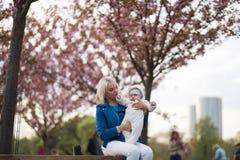 Giovane donna della madre che gode del tempo libero con il suo bambino bianco caucasico bambino del neonato con la mano di un gen immagine stock