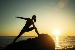 Giovane donna della siluetta di yoga che fa gli esercizi di forma fisica sulla spiaggia fotografia stock