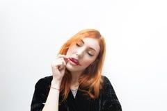 Giovane donna della testarossa che assaggia peperoncino rovente immagine stock