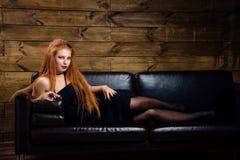 Giovane donna della testarossa che posa sul sofà Fotografie Stock