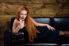Giovane donna della testarossa che posa sul sofà Fotografia Stock Libera da Diritti
