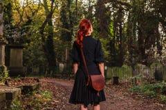 Giovane donna della testarossa che sta nel cimitero immagini stock libere da diritti