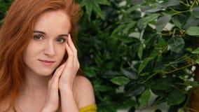 Giovane donna della testarossa che tocca il suo fronte, fondo verde immagine stock