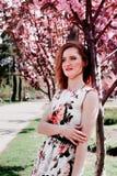 Giovane donna della testarossa nel giardino di fiori di primavera Sorgente Sakura Fotografia Stock Libera da Diritti