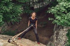 Giovane donna dello scalatore che sta sulla roccia di pietra Fotografia Stock Libera da Diritti
